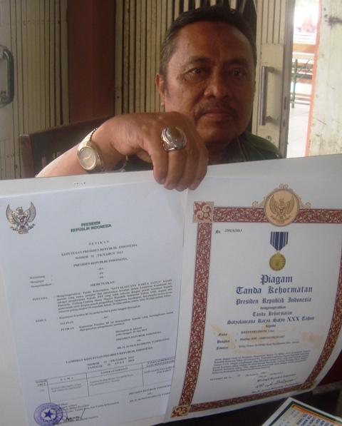 Lurah Kubu Gadang Bakhtaruddin dengan bangga memperlihatkan Piagam Satya Lencana Pengabdian 30 Tahun.