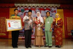 Ny. Maria Hendri Arnis menerima penghargaan Bunda Genre dari BKKBN diserahkan Kepala Perwakilan BKKBN Provinsi Sumatera Barat H.Nofrijal,MA.