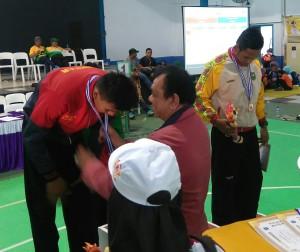 Ketua DPRD Sumbar Hendra Irwan Rahim saat mengalukan medali.