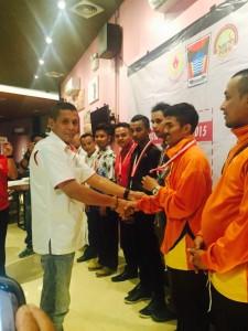 Ketua KONI Padang Agus Suardi mengalukan medali.