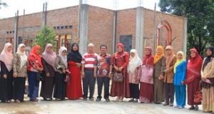 Keluarga SMPN 4 Payakumbuh foto bersama dengan Wulan Denura dengan latar belakang rehap Mushalla yang sedngan terbengkalai