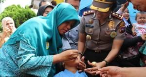 Ketua TP-PKK Payakumbuh Ny. Dr. Henny Riza falepi bersama Kapolresta AKBP Yuliani, SH, memberikan vaksinasi polio kepada seorang balita, dalam acara PIN di Kelurahan Sungai Durian Latina
