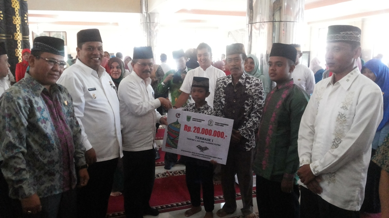 Bupati Ali Mukhni didampingi Wabup Suhatri Bur serahkan bonus uang 20 juta kepada Fadlan Mubarak, Peraih Terbaik I Tahfidz dan Tilawah Putra di Mesjid Agung Syekh Burhanuddin Jumat (1/4).