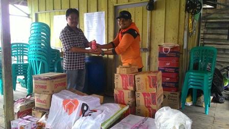 Suardi, Relawan Nusantara RZ Pekanbaru menyerahkan bantuan pada Hatta, PJS Kepala Desa Tanjung Baru yang terkena musibah longsor.