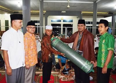 Bupati Limapuluh Kota Irfendi Arbi menyerahkan bantuan tikar pada pengurus Masjid Al-Muttaqin Balai Rupih Nagari Simalanggang Kecamatan Payakumbuh, Sabtu(18/6) malam.