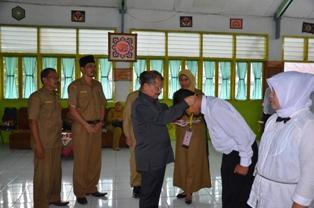 Bupati Ali Mukhni disaksikan Kabandiklat Prop. Sumbar Rosman Efendi mengalungkan tanda peserta Diklat Prajabatan kepada salah seorang peserta di Kampus INS Kayu Tanam (19/7).