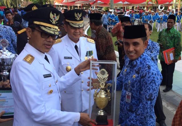 Gubernur Sumbar Irwan Prayitno serahkan trofi dan piagam penghargaan kepada Kadis Dukcapil M. Fadhly yang meraih Peringkat pertama Pelayanan Prima dan Inovasi Pelayanan Publik di Halaman Kantor Gubernur di Padang, Rabu (17/8).