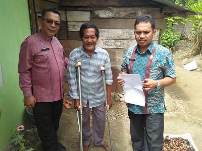 Sekretaris Dinas Sosial Nakertrans H Saiful SP dan Kasi Pelayanan dan Rehabilitasi Sosial Wifrianto serahkan tongkat ketiak ke Afrizal, 54 warga Kurai yang menderita kaki lemah