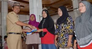 wawako menyerahkan bantuan dalam bentuk buku tabungan BTN kepara penerima bantuan rumah swadaya