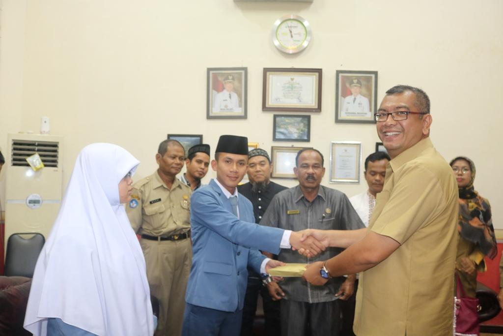 Walikota Riza Falepi menyalami dua pelajar SMA IT ICBS yang akan betolak menunaikan Umrah, disaksikan Kadisdik Hasan Basri.