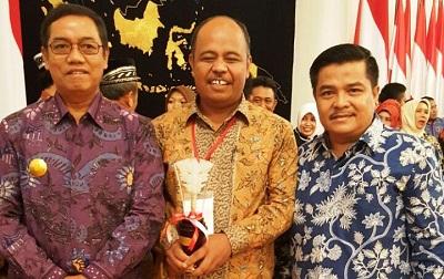 Petani Payakumbuh, Joni Saputra, didampingi Plt. Walikota Priadi Syukur dan Sekdako Payakumbuh Benni Warlis memegang penghargaan APN yang baru diterimanya dari Presiden RI Joko Widodo