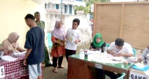 Hendra penyandang disabilitas tuna netra memilih di TPS 4 Kelurahan Padang Tinggi Piliang, Kota Payakumbuh Sumatera Barat dibimbing oleh ibunya.
