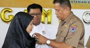 Pin Panitia Hasanah Azera Ssi Apt dilekatkan oleh Kadis Kesehatan Payakumbuh Elzadaswarman